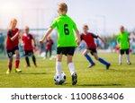 boys kicking soccer match on... | Shutterstock . vector #1100863406