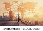 Small photo of Side view of a thoughtful businessman standing on the rooftop of a skyscraper looking over the big city at sunset with a world map hologram projection. Cryptocurrency concept. Double exposure.