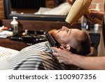 barber does haircut for bearded ... | Shutterstock . vector #1100907356