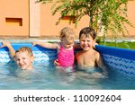 Two brothers and baby sister swimming in the pool - stock photo