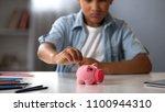 little boy putting pocket money ... | Shutterstock . vector #1100944310