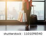 Small photo of Advertising, Business, Travel, Shopping Concept - Cropped image of woman standing at the window in airport while carrying suitcase, shopping bags, passport and boarding pass. Copy space / Select focus