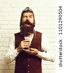 Small photo of handsome bearded aviator man with long beard and mustache on funny face holding glass of alcoholic shot in vintage suede leather waistcoat with hat and glasses on white brick wall background.