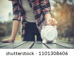 Small photo of woman hand putting coin into piggy for saving money wealth. financial concept. piggy bank. cumulative. Coin. Vintage style.Copy space.