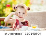 cute girl eating yogurt with... | Shutterstock . vector #110140904