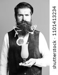 Small photo of handsome bearded man with colorful tubes in long beard and mustache has stylish hair on serious face holding glass of alcoholic cocktail in vintage suede leather waistcoat on red studio background.