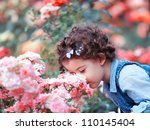 Stock photo portrait of a two year old little girl outdoor in a rose garden smelling the flowers 110145404