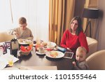 mother and sons in a restaurant | Shutterstock . vector #1101555464
