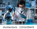 researcher holding pipette and... | Shutterstock . vector #1101628643