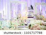 Small photo of Beautiful wedding cake on table with artificial flowers and dais as background