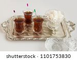 Small photo of Traditional Turkish tea in the stylish,crystal tea glass on the silver tray with white cube sugar.White surface,close up taken,isolated.Special serv when traditional festivals(Bayram)