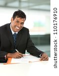 Portrait of an Indian business man working with his Digital Tablet. - stock photo