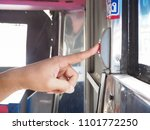 """Small photo of BANGKOK THAILAND- 16 May 2018 : finger pressing or pushing on Stop request button in bus. """"Please pushing stop request button"""" Thai word."""
