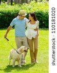 Stock photo happy couple walking golden retriever dog on park lawn smiling 110181020