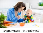 mother feeding child. first... | Shutterstock . vector #1101825959