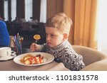 kid eating in the restaurant | Shutterstock . vector #1101831578