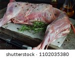 whole raw lamb and knife on the ... | Shutterstock . vector #1102035380