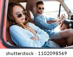 Small photo of selective focus of beautiful upset woman sitting in car with her boyfriend