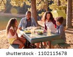 family camping by lake on... | Shutterstock . vector #1102115678