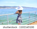 lady in hat on the pier of... | Shutterstock . vector #1102165100