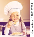 Small photo of Little girl in cook hat with milk and oatmil kasha