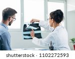 doctor and patient looking at x ... | Shutterstock . vector #1102272593
