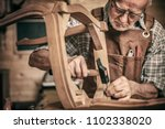elderly carpenter builds a classic style chair - stock photo