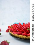 Small photo of Delicious tart with strawberry on wooden background