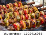 kebabs cooking on a grill on a... | Shutterstock . vector #1102416056