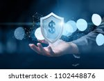 hand shows a shield with dollar ... | Shutterstock . vector #1102448876