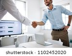 Small photo of Business colleagues shaking hands in the conference table. Happy businessman greeting colleague in the meeting room.