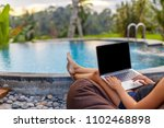 Close up woman is sitting near the pool with laptop. girl with a laptop in a lounge chair near the swimming pool. casual woman relaxing with a laptop on vacation. natural soft light