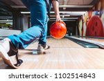 Small photo of Man throwing ball in bowling alley. View from behind