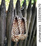 Small photo of two ancient bast shoes on the wooden fence