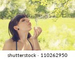 Young woman blow bubbles in the meadow - stock photo