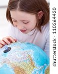 Learning about the world - young girl with earth globe - stock photo