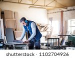 a man worker in the carpentry... | Shutterstock . vector #1102704926