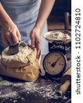baker weighing flour on a scale | Shutterstock . vector #1102724810