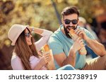 couple eating sandwich outdoors ... | Shutterstock . vector #1102738919