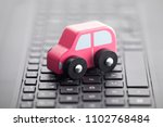 wooden car toy on laptop... | Shutterstock . vector #1102768484