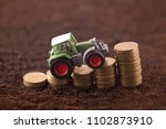 tractor miniature with coins on ... | Shutterstock . vector #1102873910