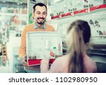 male shop seller offering cage... | Shutterstock . vector #1102980950