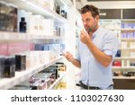 elegant man choosing perfume in ... | Shutterstock . vector #1103027630