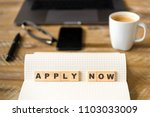Small photo of Closeup on notebook over wood table background, focus on wooden blocks with letters making Apply Now text. Concept image. Laptop, glasses, pen and mobile phone in defocused background