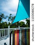 Small photo of Islamorada, FL / USA - 03/20/2018: tropical deck view of colorful lawn chair, aqua sunshade, white railing, forrest, and blue sky with clouds