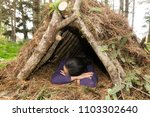 Young woman sleeps in a natural materials survival shelter in the forest - stock photo