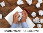 Crumpled paper and businessman tearing up another paper ball for the pile - stock photo