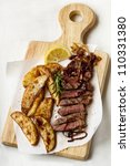 Sliced beef steak with potato wedges, onions, rosemary and lemon, on a board. - stock photo