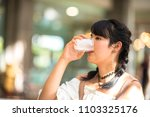 asian teenage girl drinking... | Shutterstock . vector #1103325176
