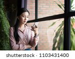a beautiful asian woman hold... | Shutterstock . vector #1103431400